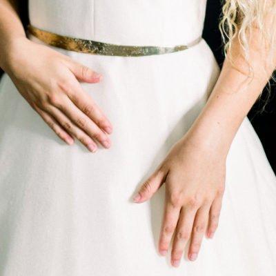 Woman wearing a white dress featuring golden waist belt