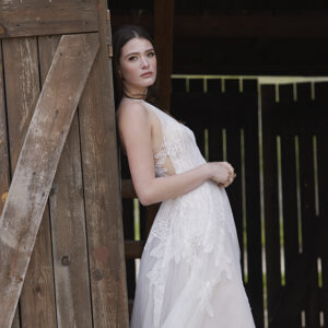 Woman in white dress agains barn door