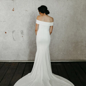 Woman wearing white dress with grey background and back turned